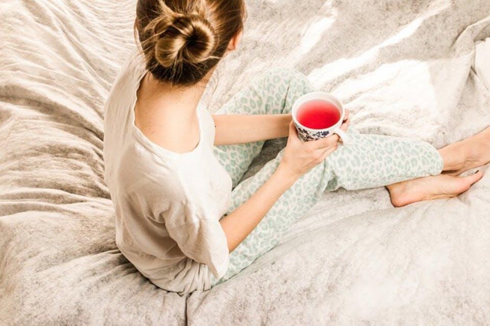 サイズの合わないナイトブラをしているベッドの上の女性