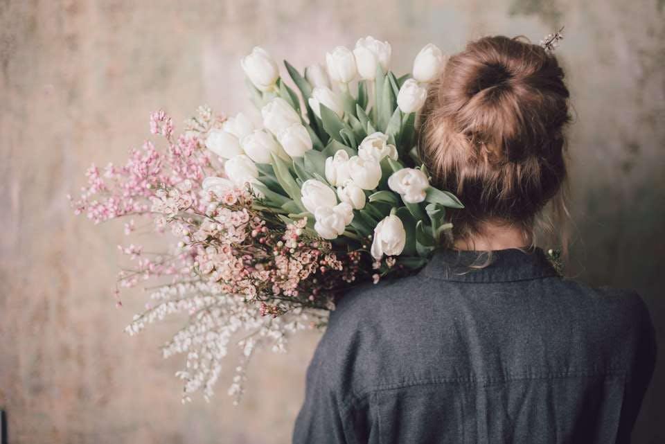 花束を抱えるお団子のおとなしい女性