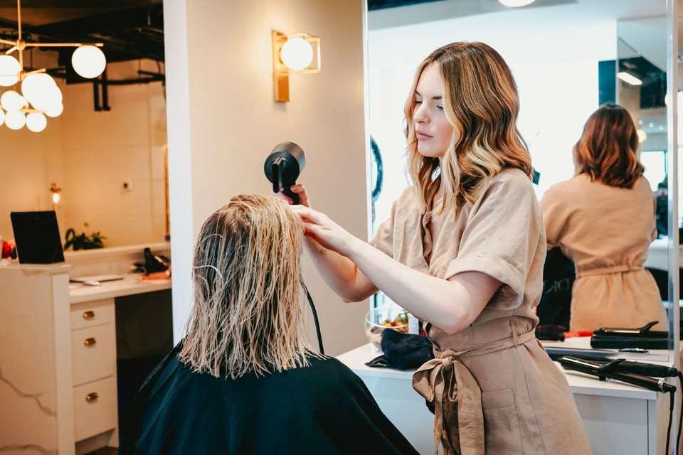 ブリーチで痛んだ髪を美容師に相談しながら市販のストレートパーマをしようか悩む金髪の人