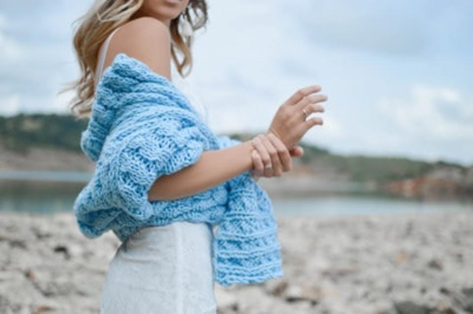 夏の白ワンピースにカーディガンを羽織った女性
