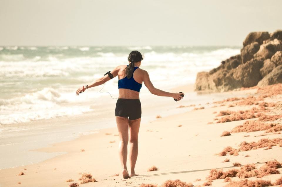 ランニング用ブラを着て浜辺を走る人