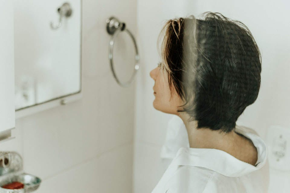顔のたるみを改善するために鏡の前でトレーニングする女性